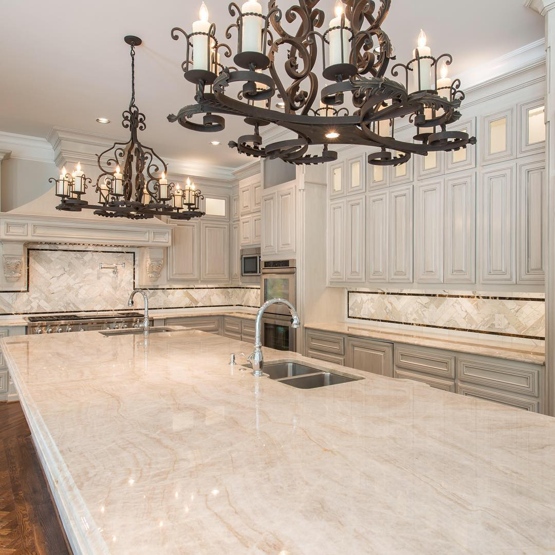 An all-white kitchen featuring granite countertops from NEKA