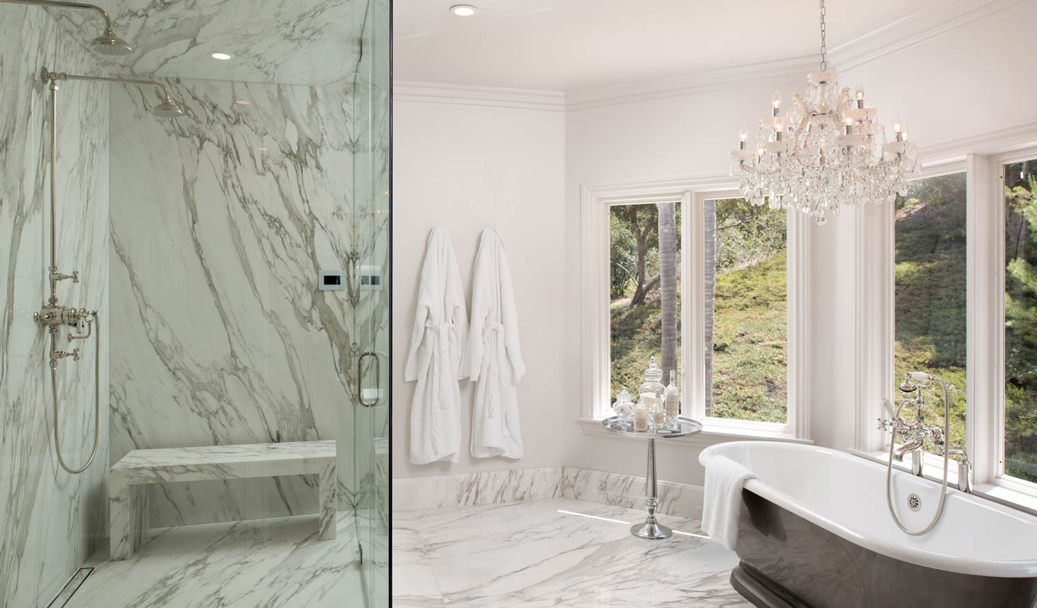 A luxury bathroom with a granite shower and granite floors.