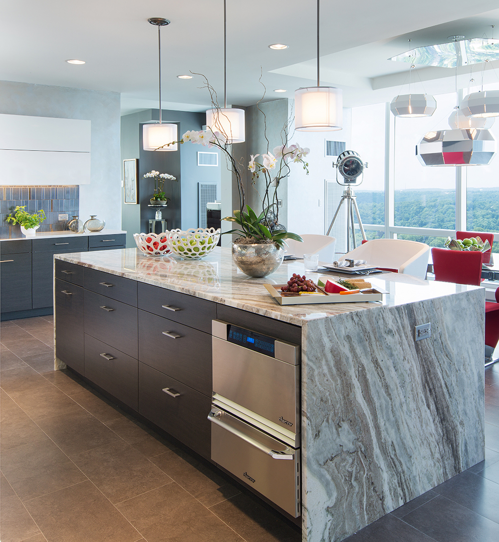 A kitchen featuring grey and white granite countertops with darker cabinets